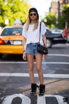 Sabrina Vuaillat in New York City wearing baseball cap, round sunglasses, oversized tee, #Chanel Boy bag, studded denim cutoff shorts, and Isabel Marant wedge sneakers | Photo by Le 21ème Arrondissement