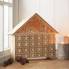 Advent calendar with battery operated lights. A beautifully refined piece of Christmas decoration made from wood with an elegant natural finish. This Christmas advent calendar not only has little draws to fill with treat and trinkets, but also has fairy lights hidden in its interior that bring alive the magical silhouette scene of Santa flying through the night sky.