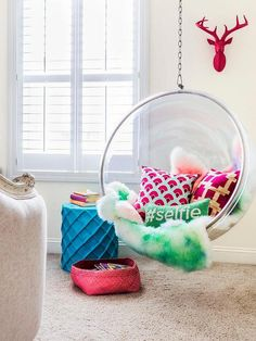 Chic teen girl's room features a pink decorative deer head over an acrylic hanging bubble chair, Candelabra Home Bolo Chair, lined with pink and green pillows next to a blue stool table, Stray Dog Designs Net Stool.