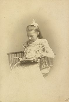 Princesa Tatiana Constantinovna, em 1900. Ela está sentada em uma cadeira de madeira e está olhando para um livro. Ela está usando um vestido modelado e tem um laço em seu cabelo.