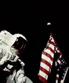 In this Apollo 17 onboard photo, Mission Commander Eugene A. Cernan adjusts the U.S. flag deployed upon the Moon. The seventh and last manned lunar landing and return to Earth mission, the Apollo 17, carrying a crew of three astronauts: Cernan; Lunar Module pilot Harrison H. Schmitt; and Command Module pilot Ronald E. Evans, lifted off on December 7, 1972 from the Kennedy Space Flight Center (KSC).
