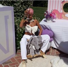 Rihanna at her cousin's baby shower, sipping champagne & sitting on a rocking elephant...lol. :D))