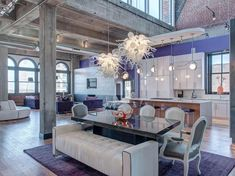 Thanks to an open floor plan, the funky dining room is the epicenter of this contemporary downtown loft. A purple accent wall outlines the dining room and kitchen, while a mix of lighting helps to define each space. The blown glass pendants above the dining table add sculptural elegance.