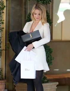 Dianna Agron was seen rifling through her YSL clutch as he carried a Dior gift bag.  (January 8, 2014)