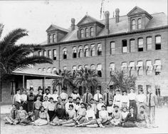 Class portrait showing Old Main and the original Normal School Building