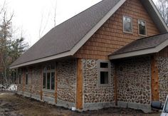 Cordwood home with wood shingle siding.  Article describes ease of building these homes and money saved compared to traditional homes.