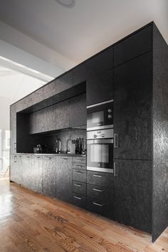 A black-painted OSB box houses a occupies a kitchen on one side in this converted barn home in Portugal.