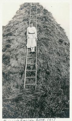 Lady on Farm STands on Ladder in Hay stack