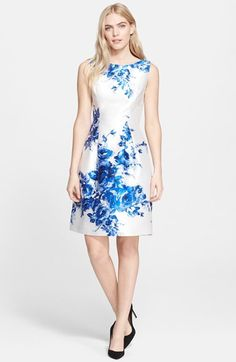 Lela Rose Flower Print Full Skirt Satin Sheath Dress - Princess seams above the natural waist and deft pleats below shape a figure-flattering sheath with a subtly full, A-line skirt. Cornflower-blue blooms stretch across the luminous silhouette, drawing attention to the ultrafeminine design.