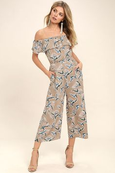 Bring a little sweetness wherever you go in the J.O.A. Traveler Beige Floral Print Midi Jumpsuit! Green, peach, and periwinkle blue floral print woven poly, shapes an elasticized off-the-shoulder neckline, short sleeves, and a flounce bodice. A banded waist with diagonal front pockets and pleated detail, rests atop flowing culotte pant legs. Open back has elastic for fit.