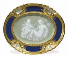 A MEISSEN PORCELAIN PATE-SUR-PATE CELADON AND COBALT-BLUE GROUND OVAL DISH<br />CIRCA 1885, BLUE CROSSED SWORDS MARK, INCISED Y.190, 19/55 AND IMPRESSED 138<br />Finely painted and hand-tooled in white slip with a grapevine-adorned Bacchante offering a saucer of wine to a putto seated atop a lion, a thyrsus in his hand, the oval surround molded and enriched with shells edged by gilt entrelac ribbons and black tracery<br />9 3/8 in. (23.8 cm.) wide <br />