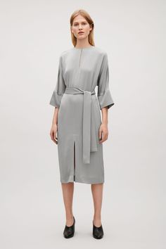 DETAILS Designed with soft, relaxed proportions, this kimono-sleeved dress is made from a shiny satin fabric with a tactile, crepe finish. Coming in at the waist, tied with a fabric belt, it is completed with simple in-seam pockets, a hidden side zip and a neat round neckline with a subtle slit and hook fastening.