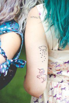 Tatuagem de chuva de corações e unicórnio na parte de trás do braço esquerdo.