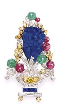AN ART DECO DIAMOND AND MULTI-GEM BROOCH, BY J.E. CALDWELL & CO. - Designed as a single and baguette-cut diamond jardinière, resting on a square-cut sapphire and circular-cut yellow diamond stand, extending a carved lapis lazuli blossom, with circular and marquise-cut diamond and yellow diamond leaves, enhanced by cabochon emerald and ruby bead berries, mounted in platinum circa 1925