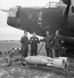 Armourers of No 75 (New Zealand) Squadron pose with a pair of 500-pounders and give the 'thumbs up' in front of the 'Wellington Devil', a suitably decorated Wellington IC, Feltwell, 10 May 1941.