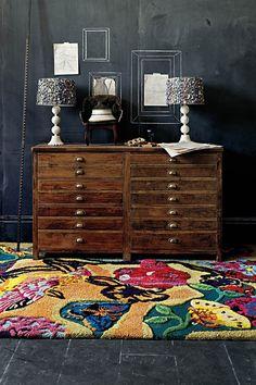 Anthropologie home decor - colorful rug, wood flat file dresser, dark