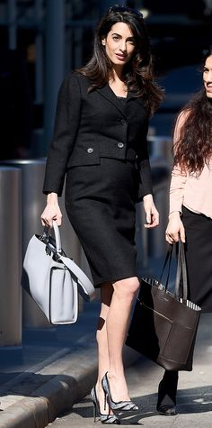 Amal Clooney proved her knack for chic maternity fashion in a tweed-like black skirt suit that consisted of a cropped blazer and matching high-waisted pencil skirt. She paired the structured pieces with a lace-lined top, co-ordinating striped Salvatore Ferragamo pumps, a sleek leather top-handle tote, and dark sunnies perched atop her head while leaving the United Nations Headquarters in New York City.