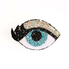 This glitter eye can be worn as either a brooch or hair clip.  Each eye is dripping in glitter and individually handmade by Kirsty in East London.