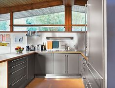 A previous owner remodeled the kitchen in outfitting it with stainless-steel cabinets by Bulthaup as well as a Sub-Zero refrigerator and an induction stove by Diva. Photo by: Spencer Lowell Metal Kitchen Cabinets, Stainless Steel Cabinets, Kitchen Windows, Kitchen Storage, New Kitchen Designs, Kitchen Ideas, Kitchen Inspiration, New Cabinet, Cabinet Ideas