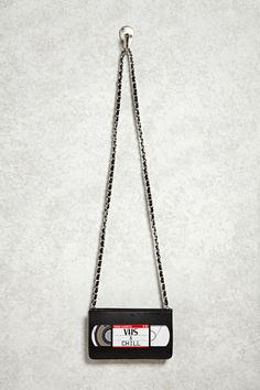 """A faux leather crossbody featuring a VHS tape design, """"VHS & Chill"""" text graphic, a zip top, and a detachable shoulder strap."""