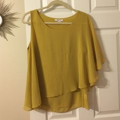 Asymmetrical Mustard Blouse This blouse has one sleeve with a butterfly sleeve that hits a little past your elbow and the other sleeve is sleeveless. Asymmetrical hemline. Minor wear in the stitching in the front. A beautiful, rich mustard color. Better Be Tops Blouses