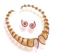 An art moderne eighteen karat gold and synthetic pink sapphire necklace and ear clips, circa 1955 the necklace designed as a series of graduated fluted gold scroll links, enhanced by circular-cut synthetic pink sapphires, and a pair of earclips en suite; necklace signed Retzignac, Caracas.