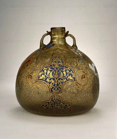 Pilgrim bottle from Syria, around 1330-1350. The shape of the bottle echoes the leather water flasks used by medieval travellers, however it was not intended to be slung from the saddle of a horse, but probably made for sale to a pilgrim to the Holy Land,seeking containers for their mementoes, as the contents (bones of saints, earth or water from sacred sites) remained safe and visible. The richly coloured enamels and gilding hide the rather poor quality of the thick,bubbly glass.