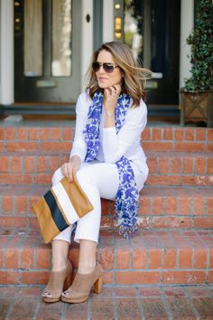 The colorful, printed scarf adds interest to the monochrome white outfit