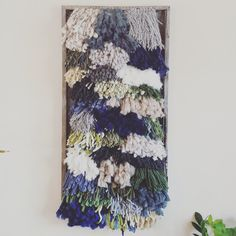 This piece is made of a variety of yarns and fibers. Colors include blue, green, gray, and earth tones. The piece measures 15x29 and is framed with reclaimed wood.