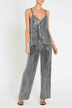 Flaunting an exclusive pinstripe sequinned fabric embellished with fine bugle beading in textured vertical stripes, this relaxed fit cami top provides the perfect party-wear come high summer. The top has metal studded piping inserted at its V-neckline edge, and contrast satin straps that can be adjusted to fit. By #sassandbide