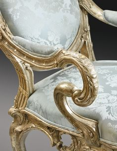 Detail A German Rococo Silvered Armchair, Attributed to Johann August Nahl, Potsdam, circa 1744-46 with an oval-shaped cartouche padded back and seat upholstered in later light blue damask silk, the carved moulded back frame with shaped pedimented crest rail topped by a pomegranate above a shell, the pronounced out scrolled arms with padded rests and gadrooned carved ends on S–shaped supports, the seat frame carved and pierced with foliage and s-scrolls, all on cabriole legs with carved…