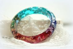 Handmade bracelet of colored resin, gold flakes, silver flakes and glitter. If the bracelet has slight imperfections, this is because it is