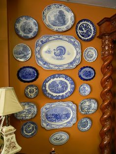 Striking display of old antique plates....really pretty against that mustard colored wall!