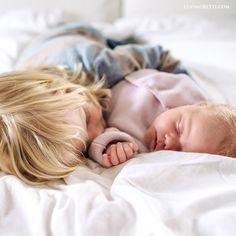 Neugeborenenfotos zu Hause mit dem großen Bruder. Baby und Bruder auf dem Bett ©️ lenimoretti.com