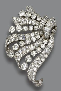 DIAMOND BROOCH, VAN CLEEF & ARPELS, NEW YORK, 1951.  The ribbon scroll set with 105 old European-cut and round diamonds weighing approximately 15.00 carats and 22 baguette diamonds weighing approximately 1.50 carats, mounted in platinum, signed Van Cleef & Arpels, numbered N.Y. 18386 S.O.