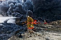 Mosul, Iraq: Firefighters try to extinguish an oil fire as smoke billows from one of the remaining wells set ablaze by Islamic State in their retreat from Qayyarah