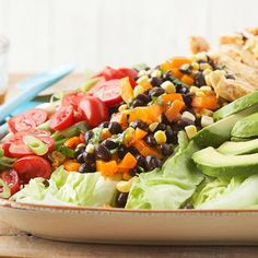 This tasty make-ahead salad recipe is perfect for parties or for a family dinner. Its colorful ingredients include lettuce, chicken, grape tomatoes, green onions, avocado, lime wedges and corn and black bean relish.