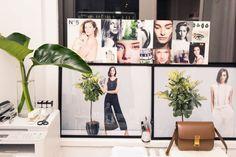 Catherine Smith Talks Online Shopping Destination Plan de Ville: Office decor of model photos, plants, and a small, tan, satchel bag | coveteur.com