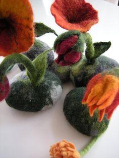 Mit grüner oder graugrüner Merinowolle umfilzter Kieselstein mit zarter Filzblüte und Blatt, als Tischdeko, für die Fensterbank oder anstatt Blumen... Die Blüten werden auf Bestellung gefilzt,...