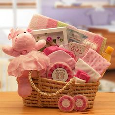 Baby Shower Gift Baskets: Moses baby carrier stuffed to the brim with pink-themed goodies including baby's first footprint kit, baby's first curl and tooth keepsake boxes, picture frame, a baby receiving blanket, two pairs of baby booties, 2 baby beanies, two 100% cotton t-shirts, baby teether, and baby's first plush animal toy. Bath items round out this practical package: Johnson & Johnson baby shampoo, and baby Q-tips in a reusable box.