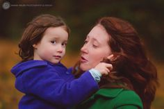 Daughter twirling Mama's hair around her finger. Fall mini session at Cathedral Park in Portland, OR. Photo by Annie Helen