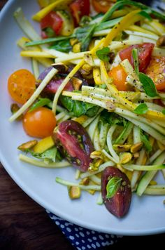 Squash Salad:  8 ounces cherry tomatoes, cut in half  1 clove garlic, thinly sliced  ¼ cup toasted pistachios  2 tablespoons torn fresh basil, plus extra leaves for garnish  2 tablespoons extra-virgin olive oil  1 teaspoon good quality balsamic vinegar  1 zucchini, thinly sliced lengthwise, then cut into ¼ inch long strips