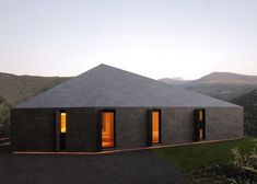 Swiss Alps home by JM Architects is covered in dark grey tiles.