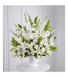 Arrangement with gladiolus, roses, bells of ireland and lilies