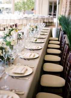 This is the dinner party look I want - capuccino linen, dark chairs, green flowers, pillar candles.