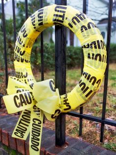 Caution Tape Wreath - wrap a foam wreath with caution tape, securing with straight pins. Add a caution tape bow. Easy peasy!