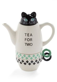 Paw Me a Cup Tea Set in Green and Black. The set includes a pair of small cups with black-and-green trim, as well as a teapot topped with a lid that looks like a cat