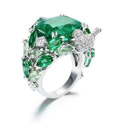 18k white gold, diamond, emerald, and tourmaline ring featuring a cushion-cut emerald center stone.