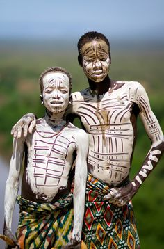 Africa | Karo Boys Showing Off; they use white river clay to make themselves beautiful or to prepare for ceremonies.  South of the Omo Valley, on the banks of the Omo River, Ethiopia | ©Steven Goethals
