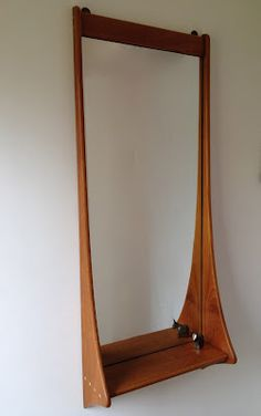 Denmark c1960 solid teak mirror with swooping sides and an integral shelf.